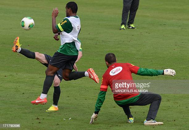 Brazil's midfielder Fernando fights for the ball with Brazil's forward Bernard as Brazil's goalkeeper Diego Cavalieri looks on during a training...
