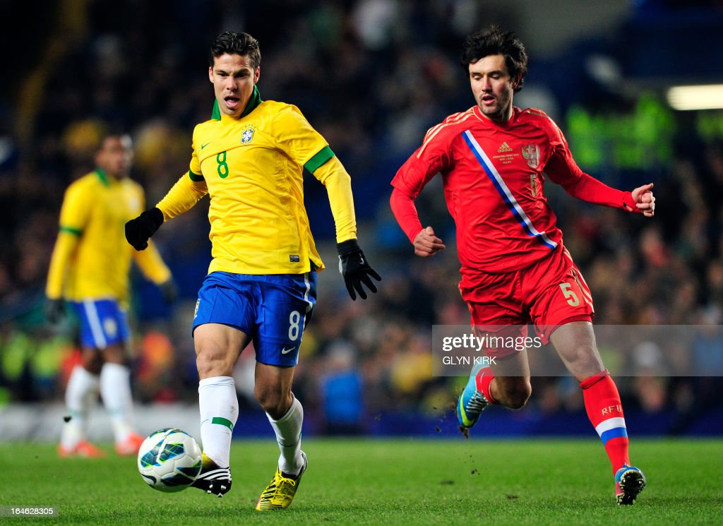 Brazil's midfielder Hernanes (L) passes the ball under pressure from Russia's midfielder Yuri Zhirkov (R) during the international friendly football match between Brazil and Russia at Stamford Bridge stadium in London on March 25, 2013. The match ended in a 1-1 draw. AFP PHOTO / GLYN KIRK