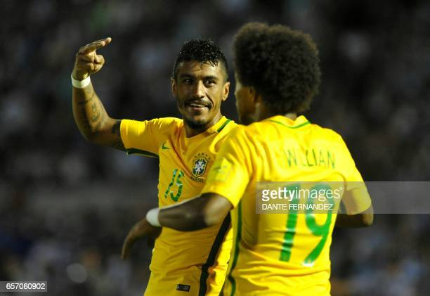 Brazil's midfielder Paulinho celebrates with teammate Brazil's midfielder Willian his second goal during their 2018 FIFA World Cup qualifier football...