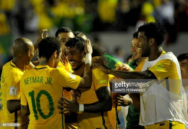 Brazil's midfielder Paulinho celebrates with teammates a goal he scored during their 2018 FIFA World Cup qualifier football match against Uruguay at...