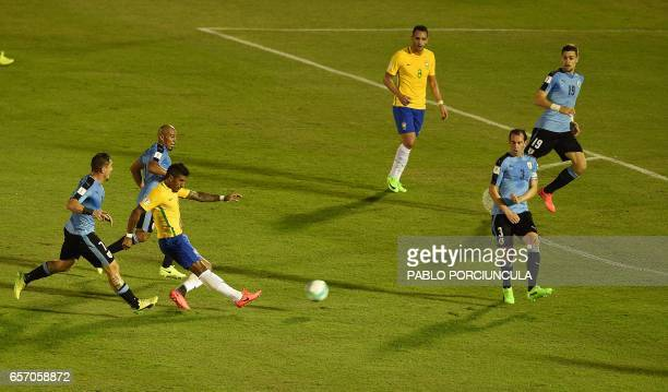 Brazil's midfielder Paulinho shoots his first goal during their 2018 FIFA World Cup qualifier football match against Uruguay at the Centenario...