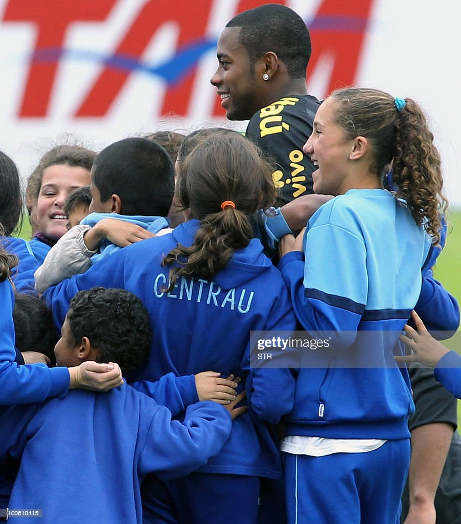 Brazil's national football team player Robinho poses with children at the end of a traning session in Curitiba, southern Brazil on May 25, 2010.