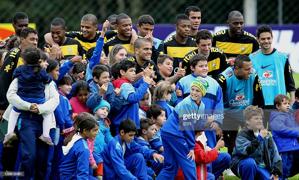 Brazil's national football team players pose with children at the end of a traning session in Curitiba, southern Brazil on May 25, 2010.