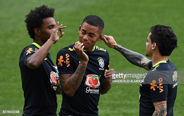 TOPSHOT Brazil's national footballers Willian Gabriel Jesus and Vagner joke during a training session in Belo Horizonte Minas Gerais Brazil on...