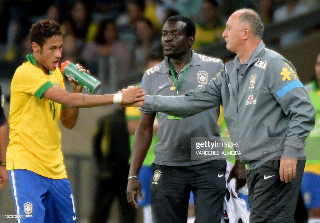 Brazil's Neymar (L) celebrates with coach Luiz Felipe Scolari after scoring against Chile, during their friendly football match at the Mineirao stadium, in Belo Horizonte, Minas Gerais, Brazil, on April 24, 2013.