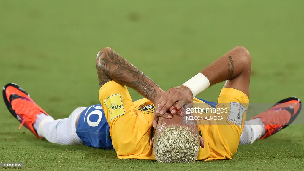 TOPSHOT - Brazil's Neymar gestures on the ground after receiving an elbow to the face by Bolivia's Yasmani Duk during the Russia 2018 World Cup football qualifier match in Natal, Brazil, on October 6, 2016. / AFP / Nelson ALMEIDA