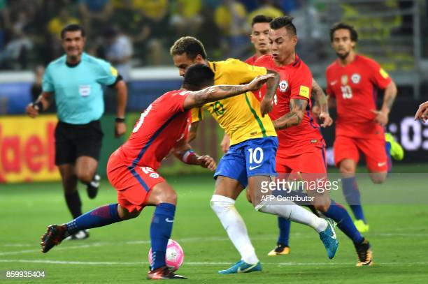 Brazil's Neymar is marked by Chile's Gonzalo Jara and Eduardo Vargas during their 2018 World Cup football qualifier match in Sao Paulo Brazil on...