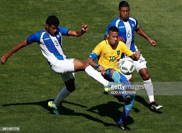 Brazil's Neymar is marked by Honduras' Marcelo Pereira and Bryan Acosta during their Rio 2016 Olympic Games men's football semifinal match at the...