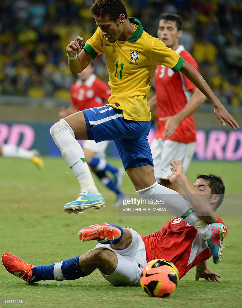 Brazil's Neymar (L) leaps over Cristian Alvarez of Chile, during their friendly football match at the Mineirao stadium, in Belo Horizonte, Minas Gerais, Brazil, on April 24, 2013. AFP PHOTO / VANDERLEI ALMEIDA