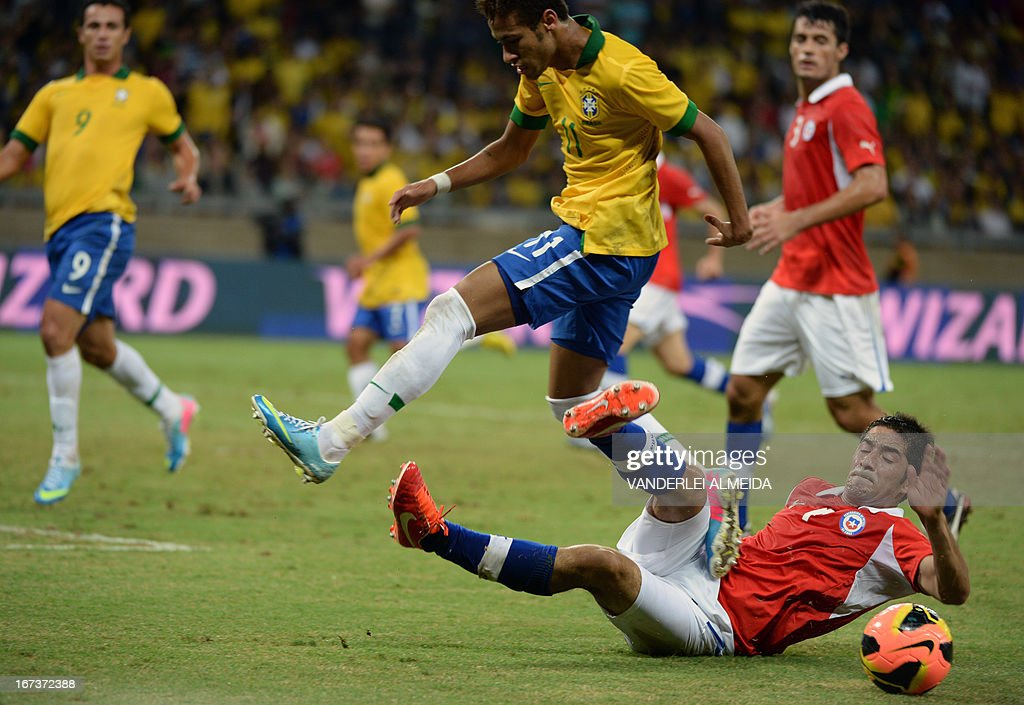 Brazil's Neymar (L) leaps over Cristian Alvarez of Chile, during their friendly football match at the Mineirao stadium, in Belo Horizonte, Minas Gerais, Brazil, on April 24, 2013. AFP PHOTO / VANDERLEI ALMEIDA