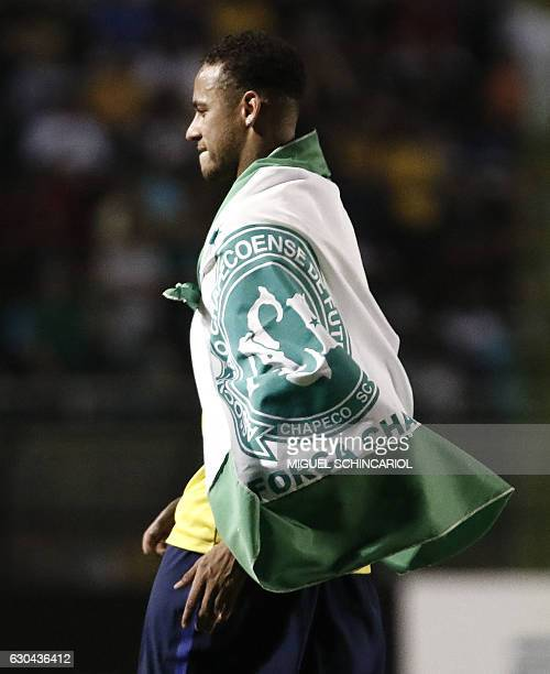 Brazil's Neymar of Spanish team Barcelona uses a flag in tribute to the victims of the November 28 2016 Colombia plane crash that killed nearly the...
