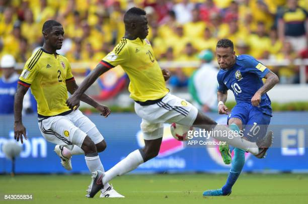 Brazil's Neymar strikes the ball as Colombia's Cristian Zapata and Davinson Sanchez look on during the 2018 World Cup qualifier football match in...
