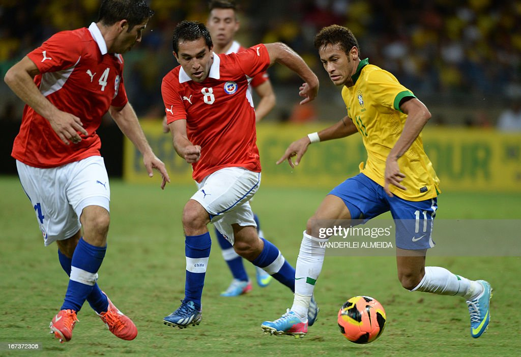Brazil's Neymar (R) vies for the ball with Cristian Alvarez (L) and Fenando Meneses of Chile, during their friendly football match at the Mineirao stadium, in Belo Horizonte, Minas Gerais, Brazil, on April 24, 2013. AFP PHOTO / VANDERLEI ALMEIDA