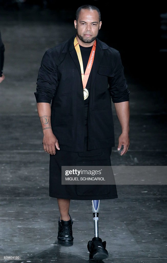 Brazil's paralympian athlete Claudinei Batista presents creations by Joao Pimenta during the 2017 Summer collections of the Sao Paulo Fashion Week in Sao Paulo, Brazil on April 28, 2016. / AFP / Miguel Schincariol