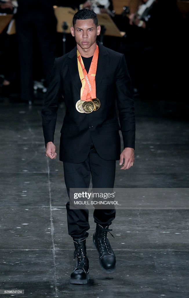 Brazil's paralympian athlete Mateus Evangelista presents a creation by Joao Pimenta during the 2017 Summer collections of the Sao Paulo Fashion Week in Sao Paulo, Brazil on April 28, 2016. / AFP / Miguel Schincariol