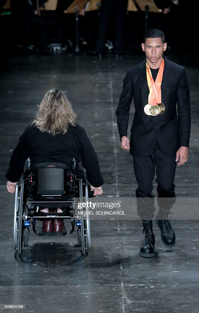 Brazil's paralympian athletes Beth Rodrigues (L) and Mateus Evangelista present creations by Joao Pimenta during the 2017 Summer collections of the Sao Paulo Fashion Week in Sao Paulo, Brazil on April 28, 2016. / AFP / Miguel Schincariol