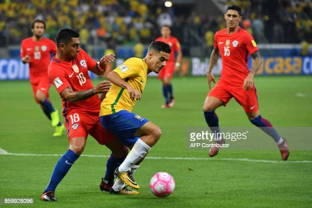 Brazil's Philippe Coutinho is marked by Chile's Gonzalo Jara during their 2018 World Cup qualifier football match in Quito on October 10 2017 / AFP...