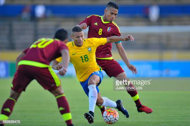Brazil's player Richarlison vies for the ball with Venezuela's player Yangel Herrera and Ronald Hernandez during their South American Championship...