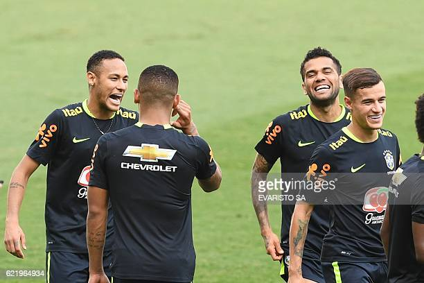 Brazil's players Neymar Daniel Alves and Philippe Coutinho joke during a training session at Mineirao stadium in Belo Horizonte Minas Gerais Brazil...