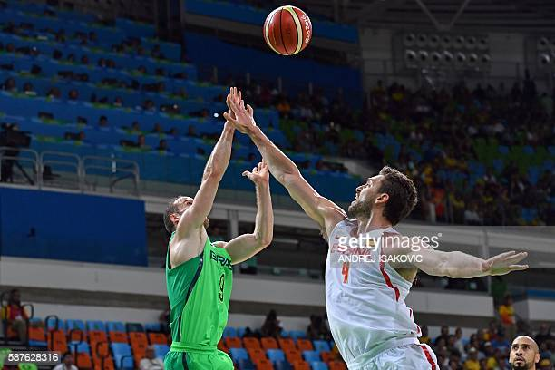 TOPSHOT Brazil's point guard Marcelinho Huertas and Spain's centre Pau Gasol go for a rebound during a Men's round Group B basketball match between...