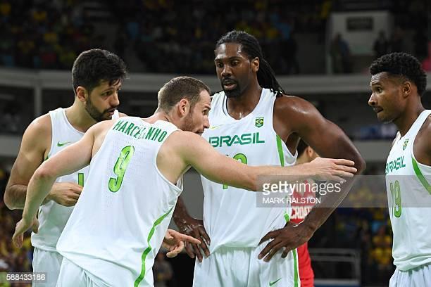 Brazil's point guard Marcelinho Huertas talks to Brazil's shooting guard Leandro Barbosa as Brazil's power forward Guilherme Giovannoni and Brazil's...