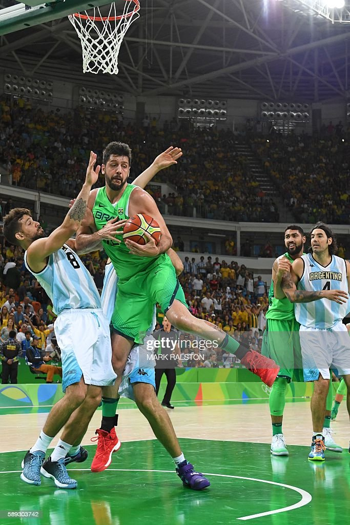 Brazil's power forward Guilherme Giovannoni holds on to the ball next to Argentina's point guard Nicolas Laprovittola during a Men's round Group B...