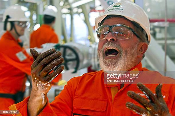 Brazil's President Luis Inacio Lula da Silva whoops for joy showing his hands dirty with the first extraction of presalt oil at the Petrobras...