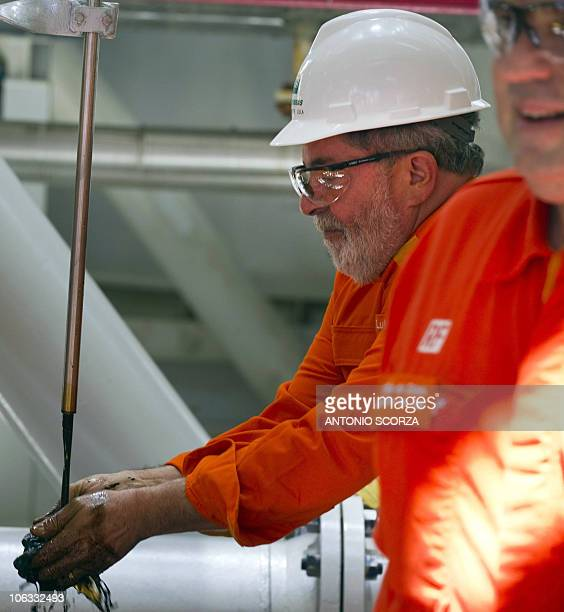 Brazil's President Luiz Inacio Lula da Silva collects with his hands the first extraction of presalt oil at the Petrobras platform RJS660/Angra dos...