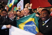 Brazil's President Luiz Inacio Lula da Silva left Rio 2016 bid President Carlos Arthur Nuzman center and Brazilian soccer great Pele right celebrate...
