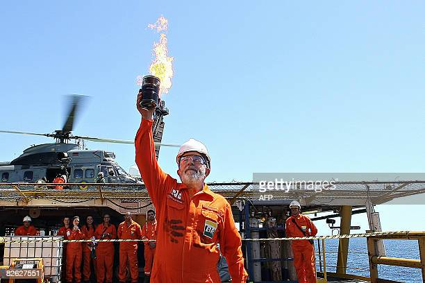 Brazil's President Luiz Inacio Lula da Silva shows the first sample of oil extracted from the very deep Jubarte oilfield reservoir offshore the state...