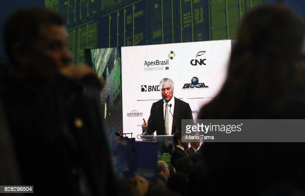 Brazil's President Michel Temer is telecast on a video screen while speaking at the National Meeting for Foreign Trade on August 9 2017 in Rio de...