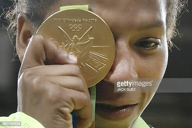 Brazil's Rafaela Silva celebrates with her gold medal following the women's 57kg judo contest of the Rio 2016 Olympic Games in Rio de Janeiro on...