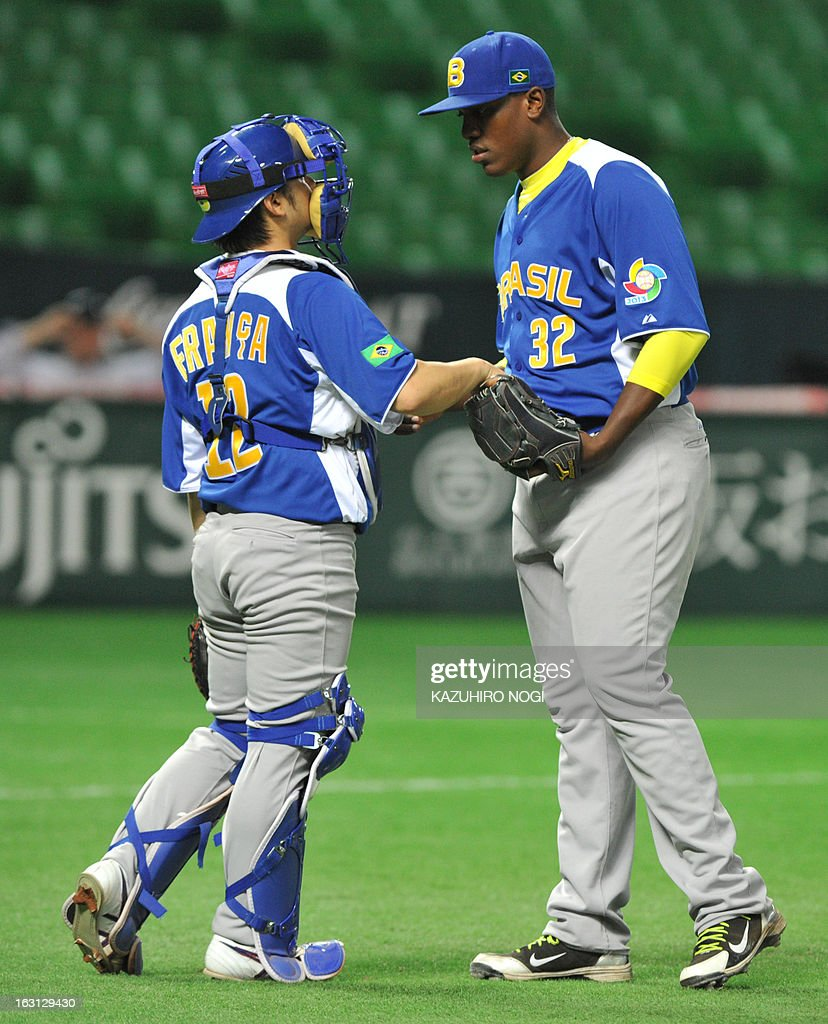 Brazil's relief pitcher Thyago Vieira (R) talks with catcher Diego Franca (L) during the eighth inning of their first-round Pool A game in the World Baseball Classic tournament in Fukuoka on March 5, 2013. China beat Brazil 5-2. AFP PHOTO / KAZUHIRO NOGI