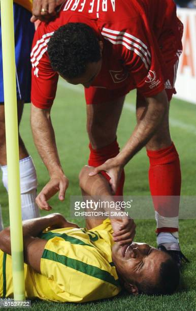 Brazil's Rivaldo reacts after a foul as Turkey's Fatih Akyel comes to his aid 03 June 2002 in Ulsan's Munsu Football Stadium during action from a...