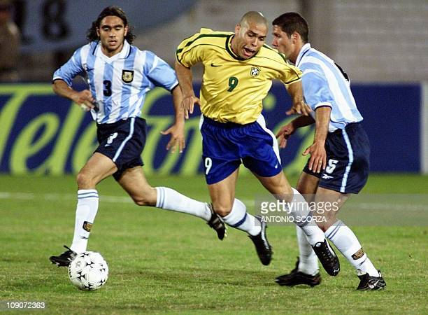 Brazil's Ronaldo is tackled by Argentina's Diego Simeone as Juan Sorin watches in their quarter final match during the Copa America Tournament 11...