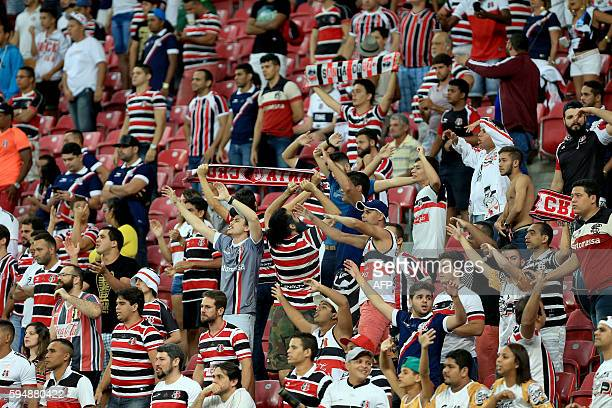 Brazil's Santa Cruz cheer for their team during the Copa Sudamericana match against Sport Recife at Arena Pernambuco stadium in Recife on August 24...