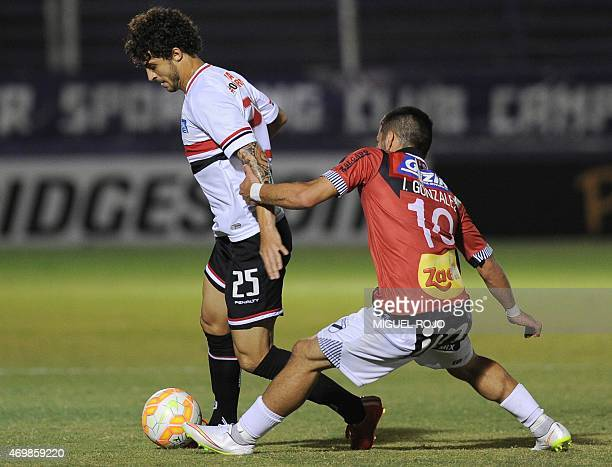 Brazil's Sao Paulo's Hudson vies for the ball with Uruguay's Danubio's Ignacio Gonzalez during their Libertadores Cup football match at the Franzini...