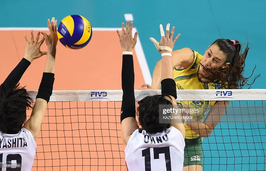 Brazil's Sheilla Castro (R) spikes the ball over Japan's Kana Ono (C) and Haruka Miyashita (L) during their volleyball match at the FIVB Women's World Grand Prix finals in Tokyo on August 24, 2014. Brazil beat Japan 3-0.