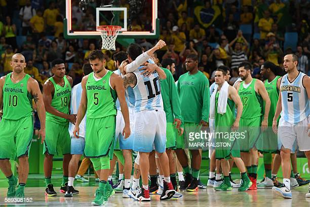 Brazil's small forward Alex Garcia Brazil's shooting guard Leandro Barbosa and Brazil's point guard Raulzinho Neto leave the court as Argentina's...
