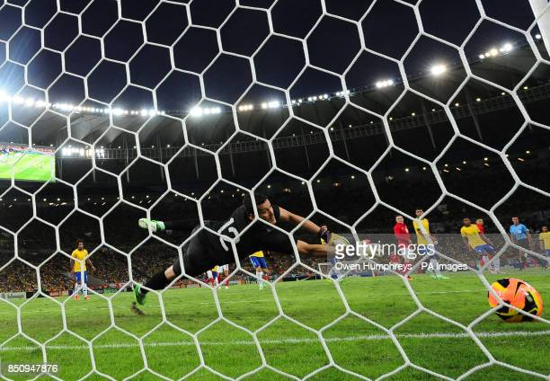 Brazil's Soares Julio Cesar cant keep out a shot from England's Alex OxladeChamberlain for England's opening goal during the International Friendly...
