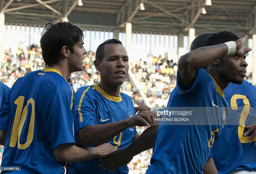 Brazil's soccer left back Michel Bastos (R) celebrates in a military way his goal as teammates Kaka(L) and Luis Fabiano look on during a friendly match with Zimbabwe at the National Sport Stadium on June 02, 2010 in Harare. Brazil's team is preparing to dispute the 2010 FIFA World Cup, in South Africa on June 11.