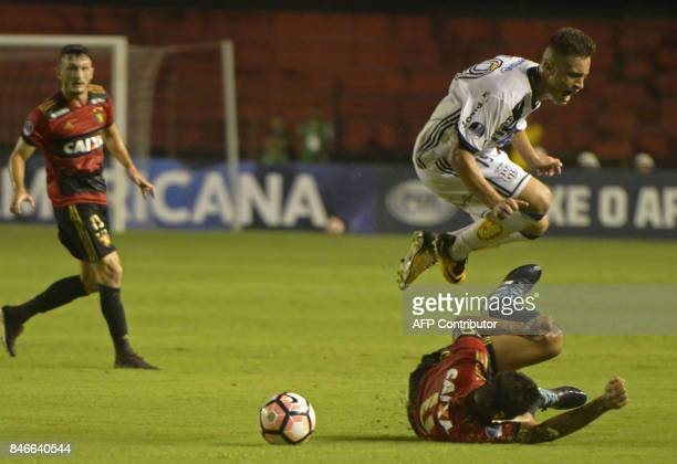 Brazil's Sport Recife Durval falls and loses the ball as Brazil's Ponte Preta Danilo Barcelo jumps to get it during the Copa Sudamericana football...