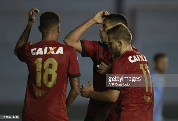 Brazil's Sport Recife forward Andre Felipe celebrates with teammates Diego Souza and Thomas after scoring against Argentina's Arsenal during their...
