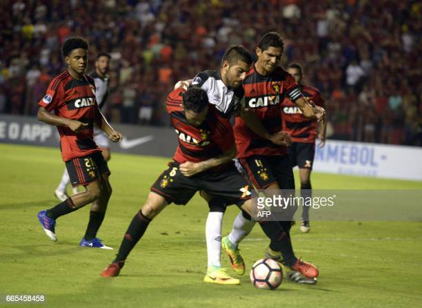 Brazil's Sport Recife players Durval and Eugenio Mena vie for the ball with Uruguay's Danubio player Joaquin Ardaiz during their Copa Sudamericana...