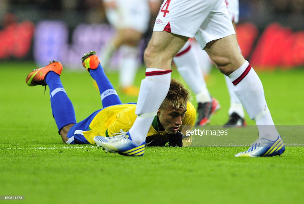 Brazil's striker Neymar (C) lies on the floor after an overhead kick during the international friendly football match between England and Brazil at Wembley Stadium in north London on February 6, 2013. AFP PHOTO / GLYN KIRK NOT FOR MARKETING OR ADVERTISING USE / RESTRICTED TO EDITORIAL USE