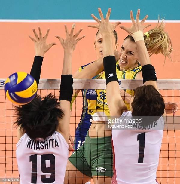 Brazil's Thaisa Menezes spikes the ball past Japan's Miyu Nagaoka and Haruka Miyashita during their volleyball match at the FIVB Women's World Grand...