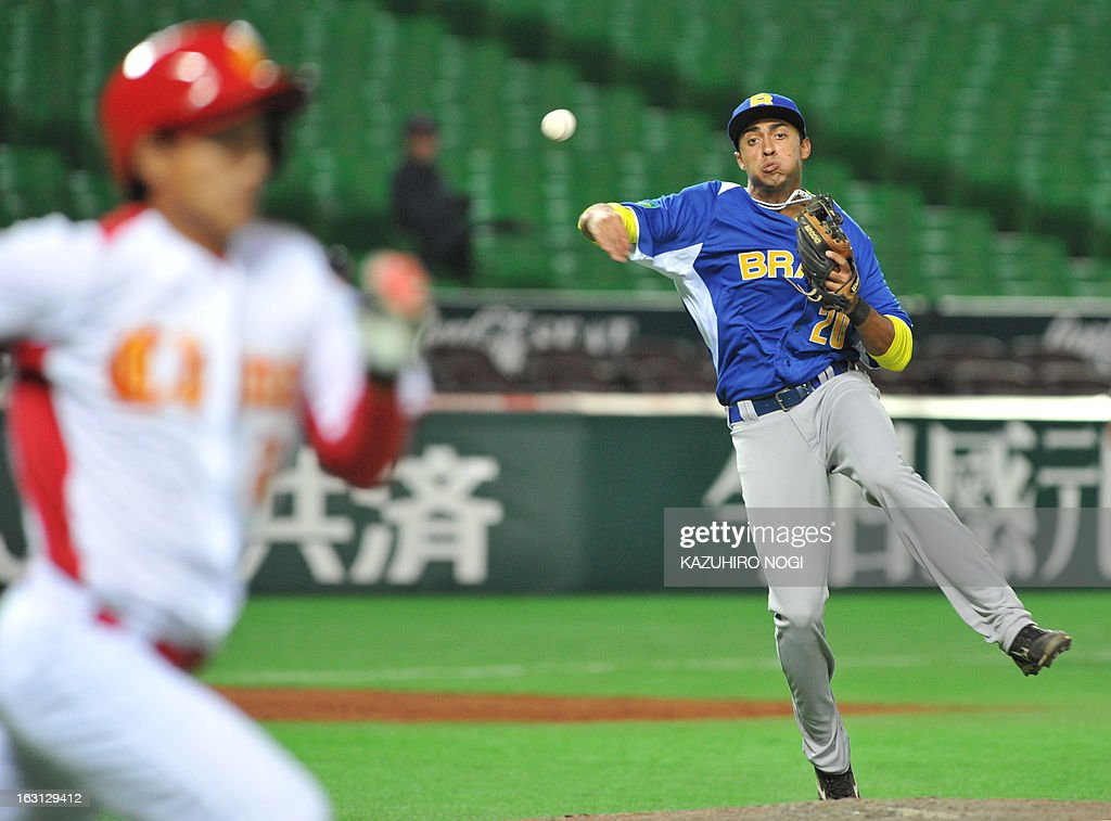 Brazil's third baseman Leonardo Reginatto (R) throws the ball while Chinese batter Chu Fujia (L) runs to the first base during the eighth inning of their first-round Pool A game in the World Baseball Classic tournament in Fukuoka on March 5, 2013. China beat Brazil 5-2. AFP PHOTO / KAZUHIRO NOGI