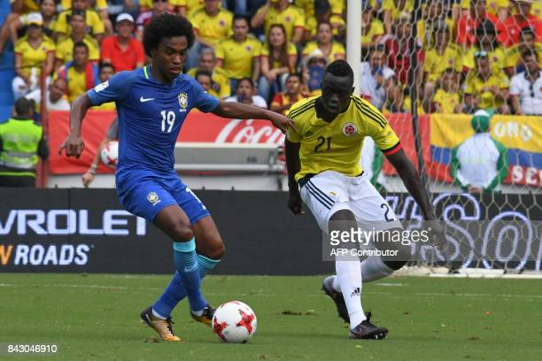 Brazil's Willian is marked by Colombia's Davinson Sanchez during their 2018 World Cup qualifier football match in Barranquilla Colombia on September...