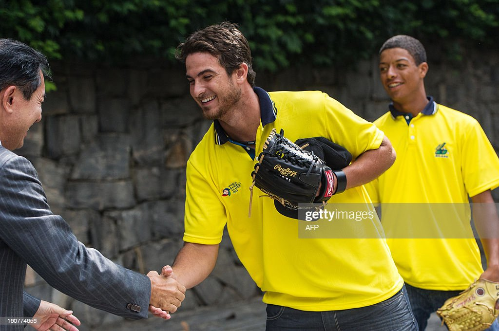 Brazlian National Baseball team player Andre Rienzo (C), also player of Chicago White Sox, greets Japanese consul general Noriteru Fukushima after showing his pitching during a reception at the Japanese consulate for their first participation in the World Baseball Classic (WBC), in Sao Paulo, Brazil, on Februrary 5, 2013. WBC first round will start from March 2 in Japan, Taiwan, Puerto Rico and the US with 16 teams from around the world taking part. AFP PHOTO/Yasuyoshi CHIBA