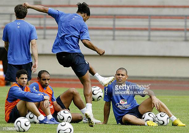 Brazlian player Ronaldinho Gaucho is watched by teammates Ronaldo Nazario Emerson and Cicinho as he practices his skills during a training session at...